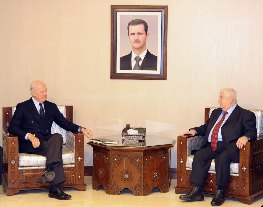 In this photo released by the Syrian official news agency SANA, Syria's foreign minister, Walid Moallem, right, meets with U.N. Special Envoy for Syria Staffan de Mistura in Damascus on Saturday.