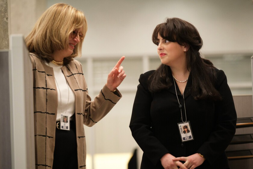 Two women talking amid office cubicles