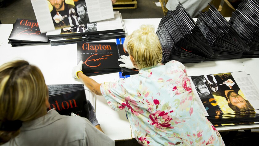 CITY OF INDUSTRY, CA -- MAY 20, 2013--Workers prepare Eric Clapton, vinyl album jackets for shipping