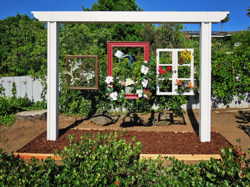 Bert and Cynthia Rhine of Poway built a large structure that suspends old picture frames and a decorated window.