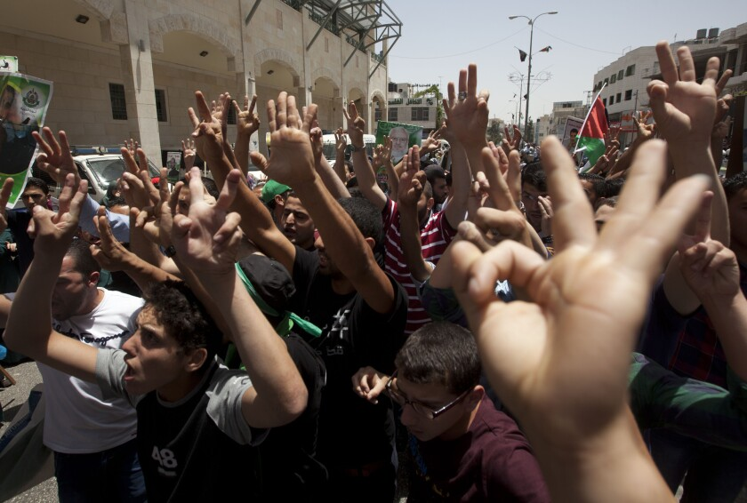 Palestinian backers of Hamas in the West Bank city of Hebron make hand gestures including three raised fingers, a sign of support for the recent abduction of three missing Israeli teens, during a protest against the arrest of 50 Palestinians by Israeli soldiers on Friday.