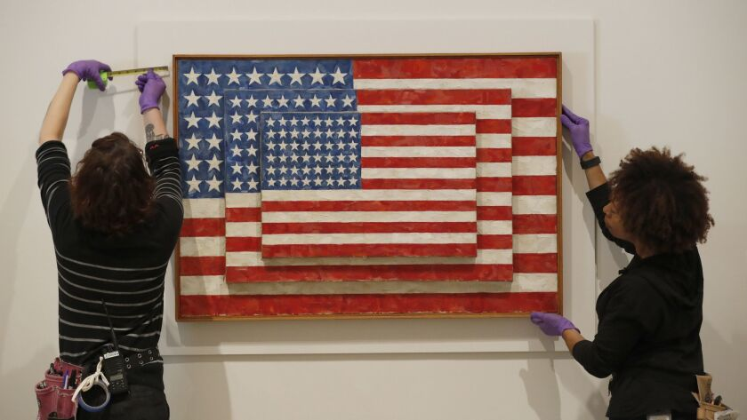 """LOS ANGELES, CALIF. -- WEDNESDAY, JANUARY 31, 2018: Installers from The Broad mount """"Three Flags,"""" b"""