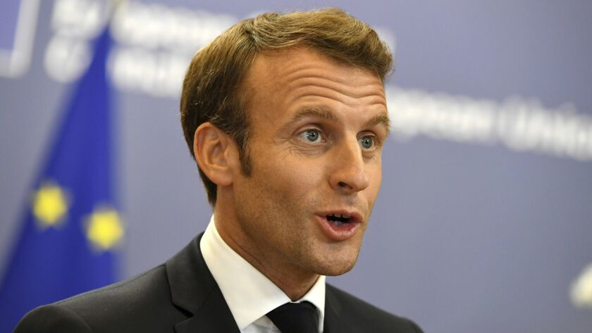 French President Emmanuel Macron speaks with the media as he leaves after an EU summit in Brussels,