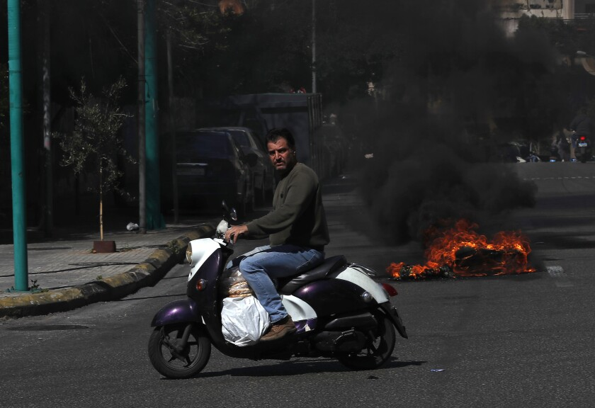 FILE - In this March 16, 2021 file photo, a man rides his scooter carrying bread as he passes in front of burning tires to block a main road, during a protest against the increase in prices of consumer goods and the crash of the local currency, in Beirut, Lebanon. on Tuesday, June 22, 2012, Lebanon's economy ministry raised the price of subsidized bread for the fifth time in a year amid the tiny country's worsening economic and financial crisis. (AP Photo/Hussein Malla, File)
