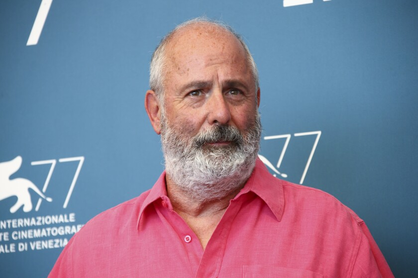 """FILE - Roger Michell poses for photographers at the photo call for the film 'The Duke' during the 77th edition of the Venice Film Festival in Venice, Italy, on Sept. 4, 2020. Michell, the British stage, television and film director whose movies include the indelibly popular romcom """"Notting Hill,"""" has died, his family said Thursday. He was 65. (Photo by Joel C Ryan/Invision/AP, File)"""