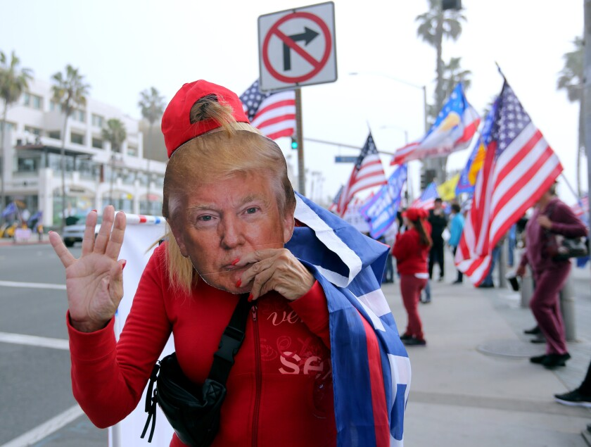 A supporter of President Donald Trump holds a mask of the commander-in-chief.