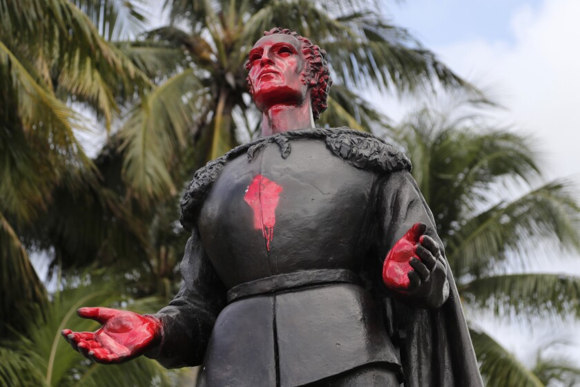 A statue of Christopher Columbus with his face and hands spray-painted red