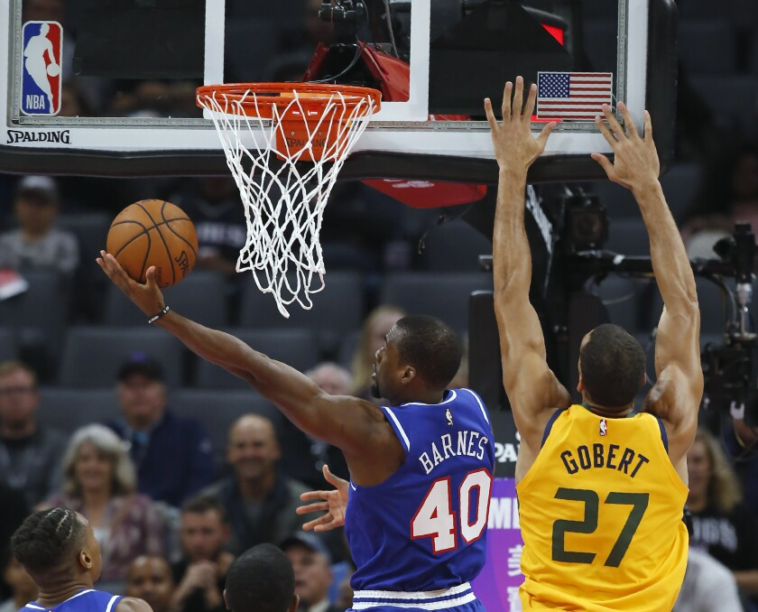 Sacramento Kings forward Harrison Barnes, left, goes to the basket next to Utah Jazz center Rudy Gobert during the first quarter of an NBA basketball game in Sacramento, Calif., Friday, Nov. 1, 2019. (AP Photo/Rich Pedroncelli)
