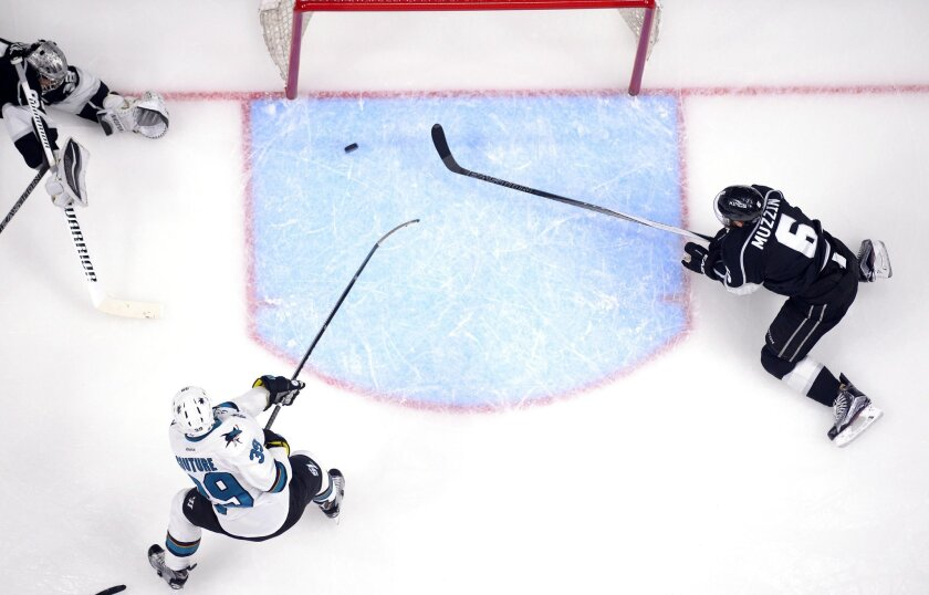 San Jose Sharks center Logan Couture, center, scores past Los Angeles Kings goalie Jonathan Quick, left, and defenseman Jake Muzzin during the second period of Game 2 in an NHL hockey Stanley Cup playoffs first-round series, Saturday, April 16, 2016, in Los Angeles. (AP Photo/Mark J. Terrill)