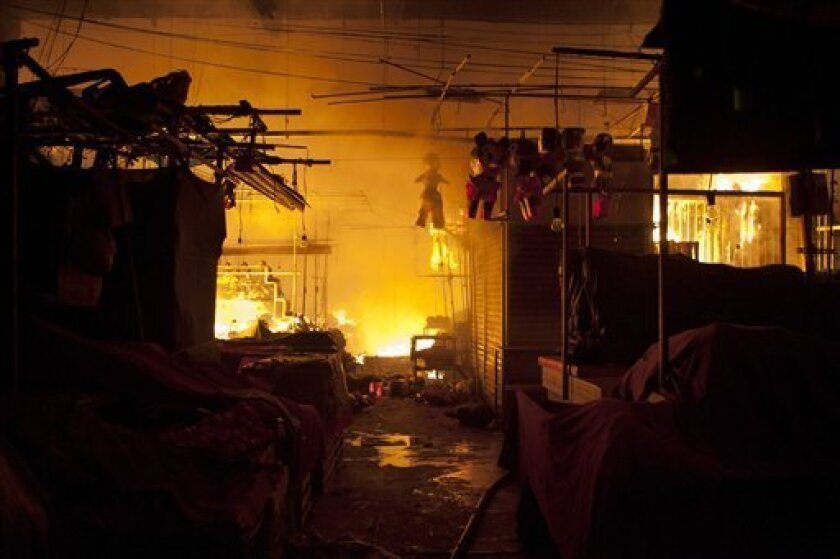 A fire consumes stalls inside the Merced market in the early morning hours of Wednesday, Feb. 27, 2013. A fire ripped through Mexico City's biggest traditional marketplace on Wednesday, causing extensive damage but no initial reports of fatalities. (AP Photo/Pepe Jimenez)