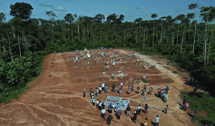 Familiares de personas que murieron por COVID-19 se reúnen junto a una fosa común clandestina en las afueras de Iquitos, Perú, el sábado 20 de marzo de 2021. Las autoridades locales aprobaron entierros masivos de víctimas de la pandemia, pero nunca se lo dijeron a las familias que creían que sus seres queridos estaban enterrados en el cementerio local cercano y solo meses después descubrieron la verdad. (Foto AP/Rodrigo Abd)