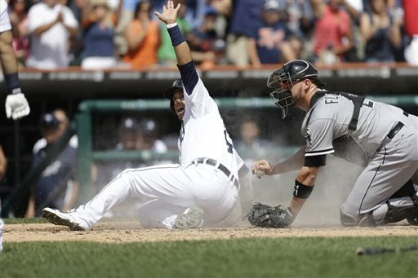 Detroit Tigers' Victor Martinez looks to the home plate umpire after beating the tag of Chicago White Sox catcher Tyler Flowers during the seventh inning of a baseball game in Detroit, Sunday, Aug. 4, 2013. (AP Photo/Carlos Osorio)