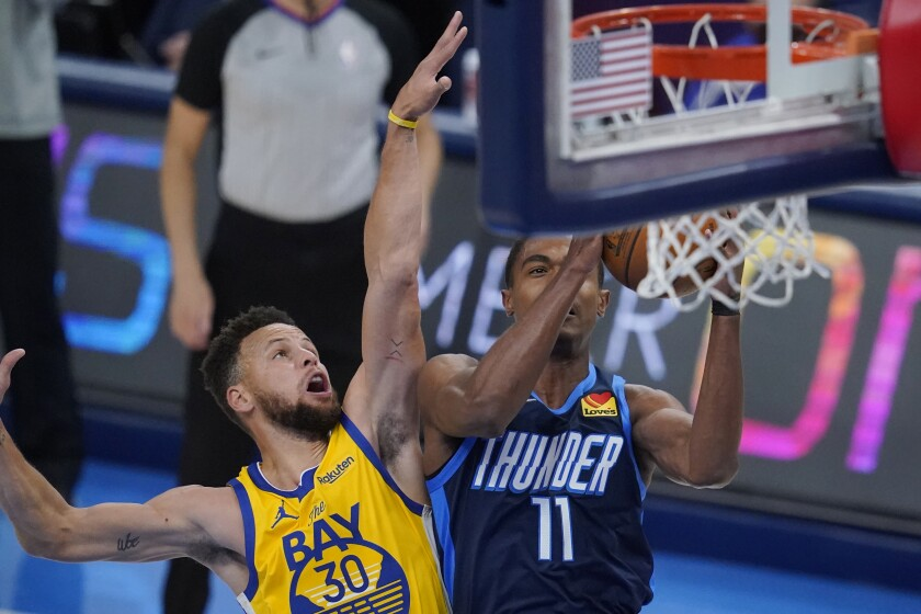Oklahoma City Thunder guard Theo Maledon (11) shoots in front of Golden State Warriors guard Stephen Curry (30) in the first half of an NBA basketball game Wednesday, April 14, 2021, in Oklahoma City. (AP Photo/Sue Ogrocki)