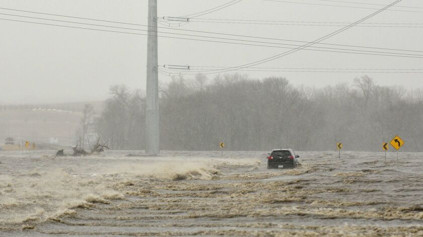 In this March 14, 2019 photo an abandoned car sits on Industrial Highway in flood waters north of No