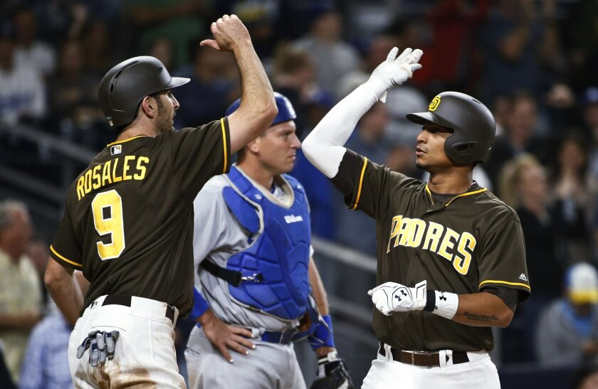 San Diego Padres' Christian Bethancourt high-fives with Adam Rosales at home plate after hitting a two-run home run against the Los Angeles Dodgers during the sixth inning of a baseball game Friday, May 20, 2016, in San Diego. (AP Photo/Lenny Ignelzi)