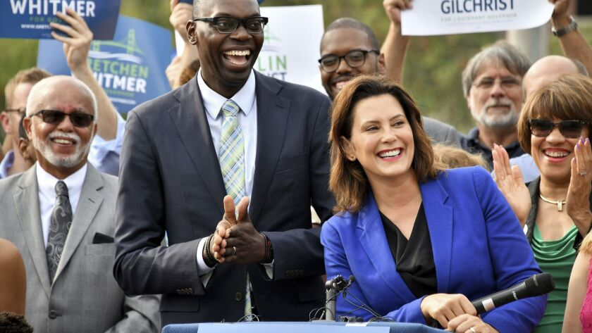 Democratic candidate for governor Gretchen Whitmer, right, announces her running mate is Garlin Gilchrist II, center, during an event in downtown Lansing, Mich., on Aug 20.