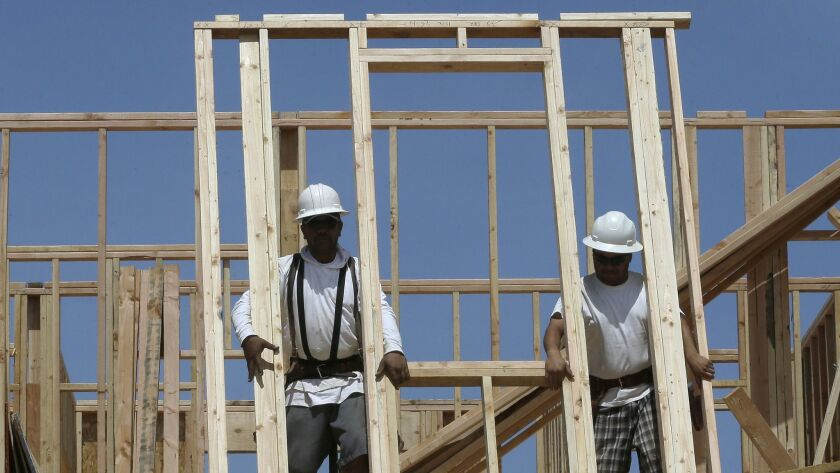 Workers raise the frame of a house under construction near Roseville, Calif.