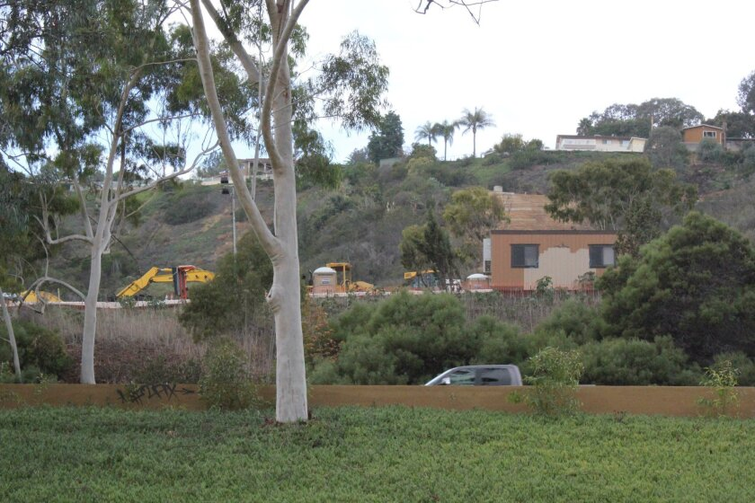 Construction crews work on a hillside below Desert View Drive, visible from Interstate 5, south of La Jolla Parkway. The San Diego Public Works Department said the outfall repair project's aim is to stop erosion in the canyon area below.