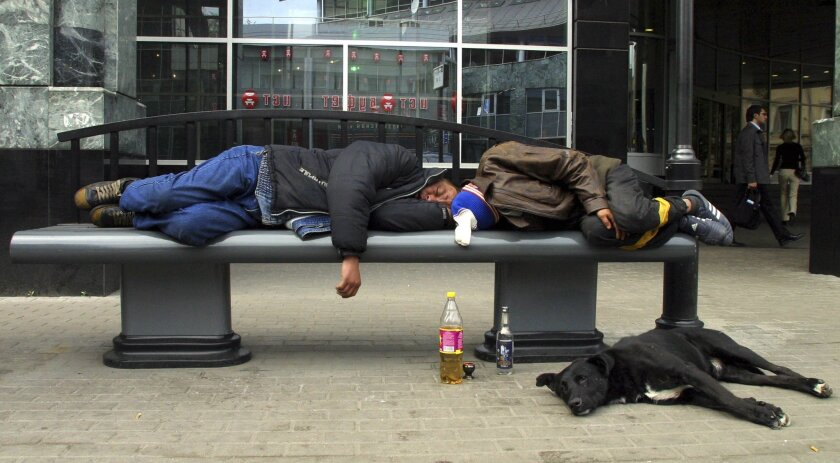 Before laws banned public consumption of alcohol, two men sleep with bottles of alcohol at hand on a Moscow street in 2005.