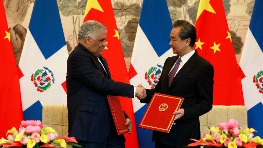 Dominican Republic Foreign Minister Miguel Vargas, left, and Chinese counterpart Wang Yi shake hands on May 1, 2018, after a signing ceremony in Beijing where they formally established diplomatic relations between the two countries.