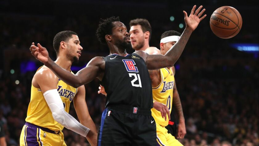 Patrick Beverley (21) of the Clippers reaches for a loose ball during the first half.
