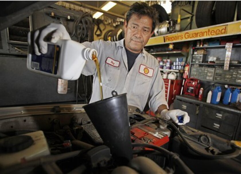 In this Oct. 4, 2011 photo, mechanic Ray Duran changes oil in a car at a Shell station in Los Angeles. Employers added 103,000 jobs in September, a modest burst of hiring after a sluggish summer. (AP Photo/Reed Saxon)
