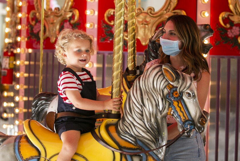 Jacques and Abigail Carrere ride the carousel at South Coast Plaza in June.