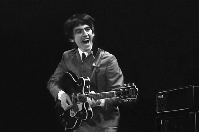 Former Beatle George Harrison, who died in 2001 at the age of 58, will be one of the 2015 Lifetime Achievement Grammy Award recipients. This February 11, 1964 photo provided by Christie's auction house, is from a collection of photos of The Beatles shot by photographer Mike Mitchell at the Washington Coliseum in Washington, D.C., shows Harrison during the group's first US concert, two days after their debut Ed Sullivan TV appearance. (AP Photo/Christie's, Mike Mitchell)