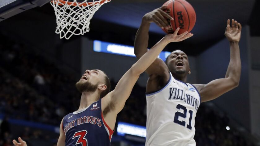 Villanova's Dhamir Cosby-Roundtree (21) blocks a shot by St. Mary's Jordan Ford (3) during the first half of a first round game in the NCAA Tournament on Thursday in Hartford, Conn.