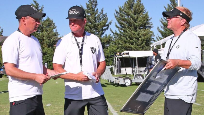 Raiders coach Jon Gruden, center, talks with his right-hand men — Mark Arteaga, left, and Jeff Leonardo — during training camp.