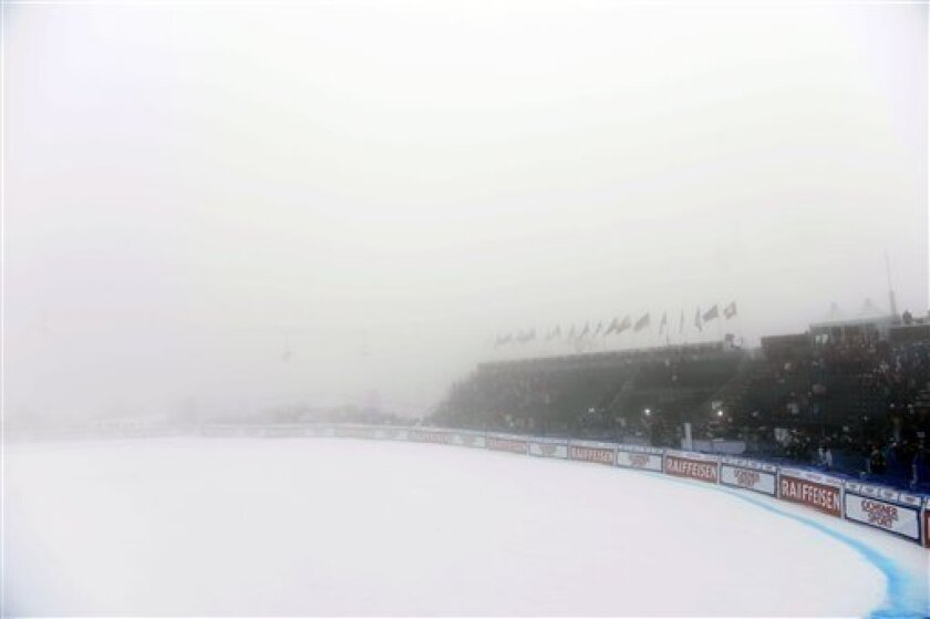 Spectators wait in a dense fog in the finish area for the start of the men's downhill race of the Alpine skiing World Cup finals, in Lenzerheide, Switzerland, Wednesday, March 13, 2013. The downhill race had to be postponed because of the fog. (AP Photo/Keystone, Laurent Gillieron)