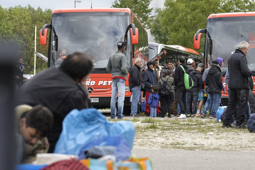 Migrants from Syria, Afghanistan and Iraq wait to board buses to other German cities outside a refugee accomodation facility in Munich on September 7.