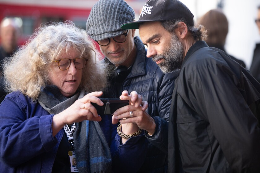 A woman and two men look at a electronic device.