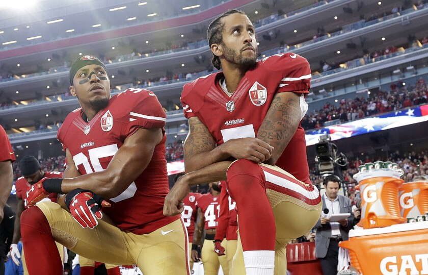 San Francisco 49ers teammates Eric Reid and Colin Kaepernick kneel during the national anthem.