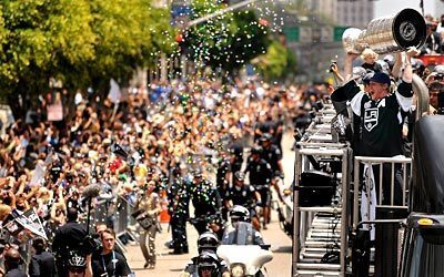 Kings defenseman Matt Greene holds the Stanley Cup aloft as the Kings victory parade makes its way down Figueroa Street.