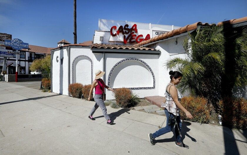 Two women walk past Casa Vega, a Mexican restaurant.