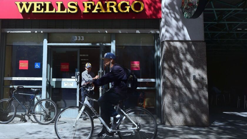 A man rides by a branch of Wells Fargo bank in Los Angeles in October 2016. The city of Los Angeles is adopting new bank disclosure requirements prompted by Wells Fargo's accounts scandal.