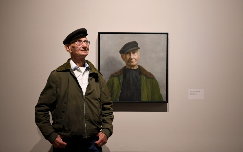 Holocaust survivor Joshua Kaufman in front of his portrait, by David Kassan, at the USC Fisher Museum of Art.