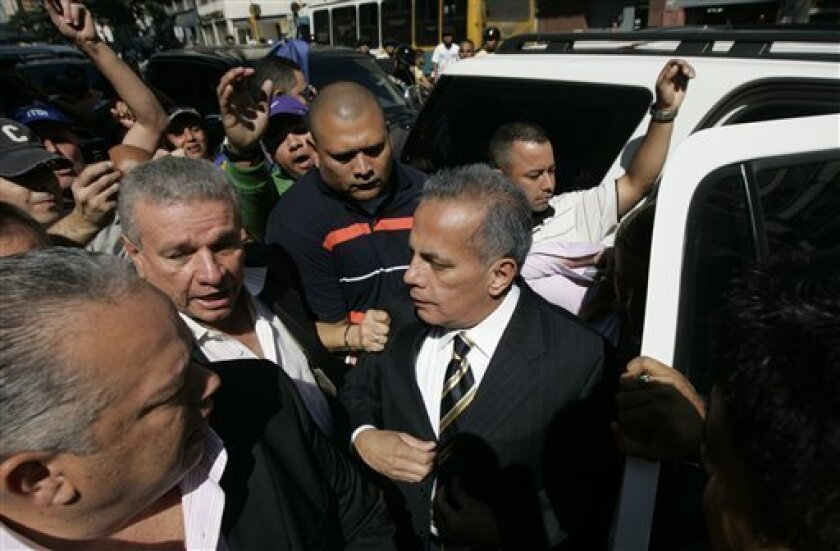 Opposition leader Manuel Rosales, center, surrounded by bodyguards, arrives to the state prosecutor's office in Caracas, Thursday, Dec. 11, 2008. Venezuelan prosecutors say they have summoned Rosales, who was elected mayor of Maracaibo, Venezuela's second-largest city, in last month's gubernatorial and municipal elections, for arraignment on corruption allegations. (AP Photo/Fernando Llano)
