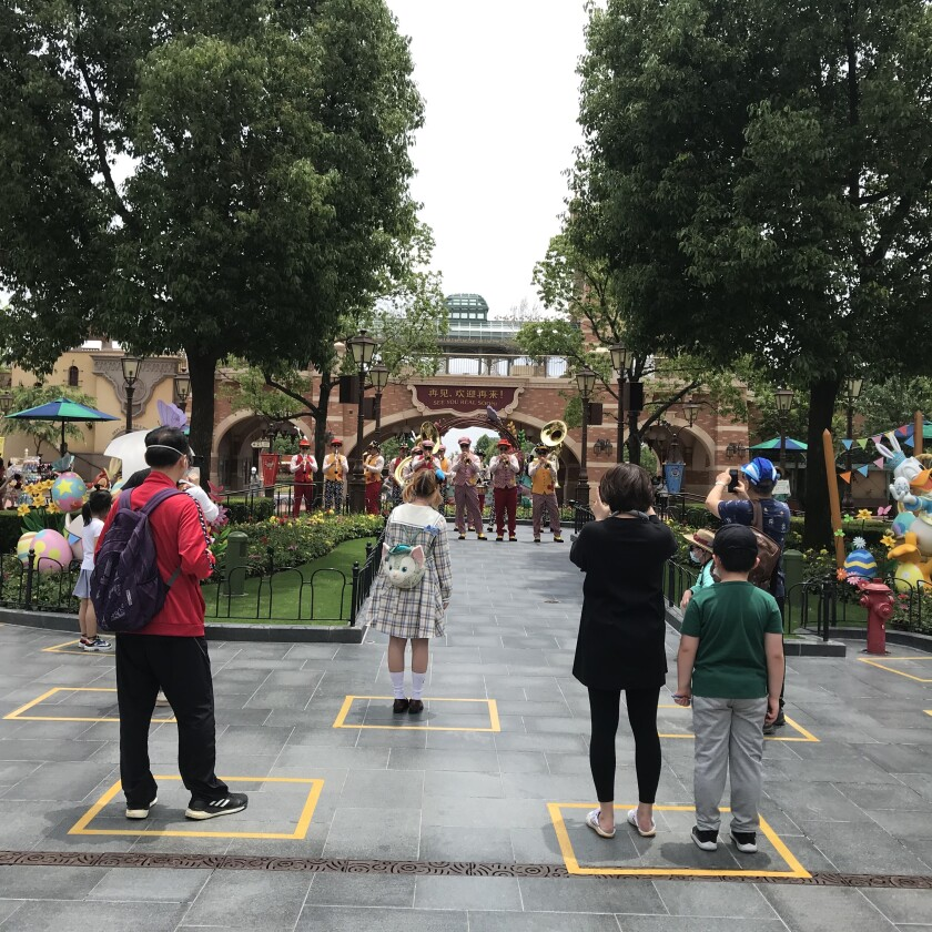 Yellow boxes are taped on the ground to maintain social distancing among visitors inside the park. One family is allowed to stand in each box.
