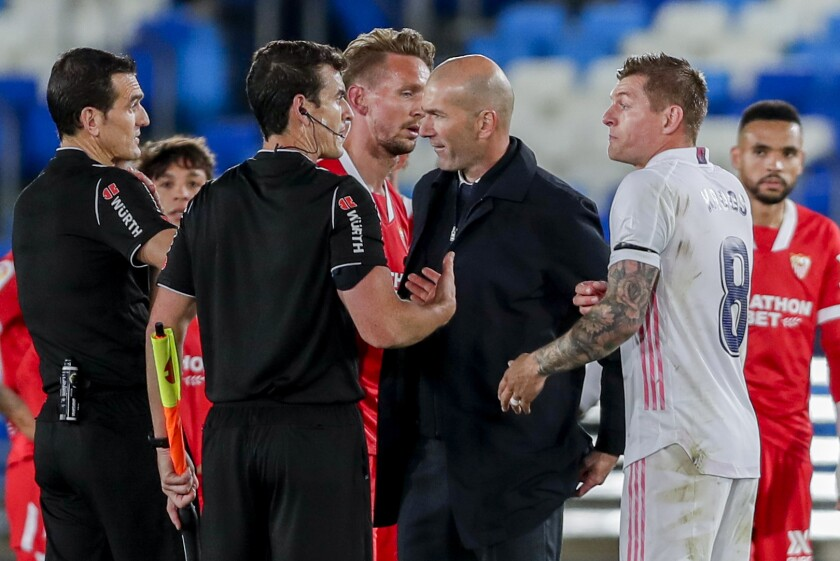 Real Madrid's head coach Zinedine Zidane talks with the referre at the end of the Spanish La Liga soccer match between Real Madrid and Sevilla at the Alfredo di Stefano stadium in Madrid, Spain, Sunday, May 9, 2021. (AP Photo/Manu Fernandez)