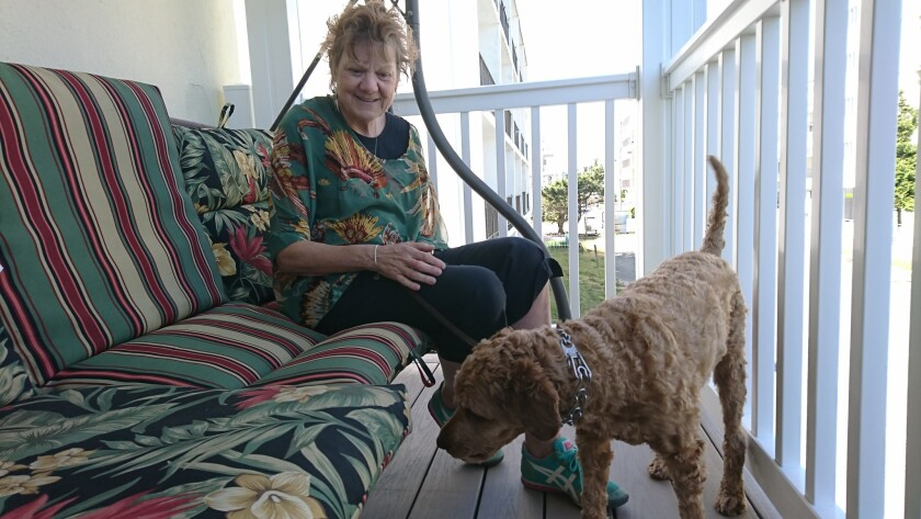 Gemma Hoskins sits on her patio with her dog, Teddy.