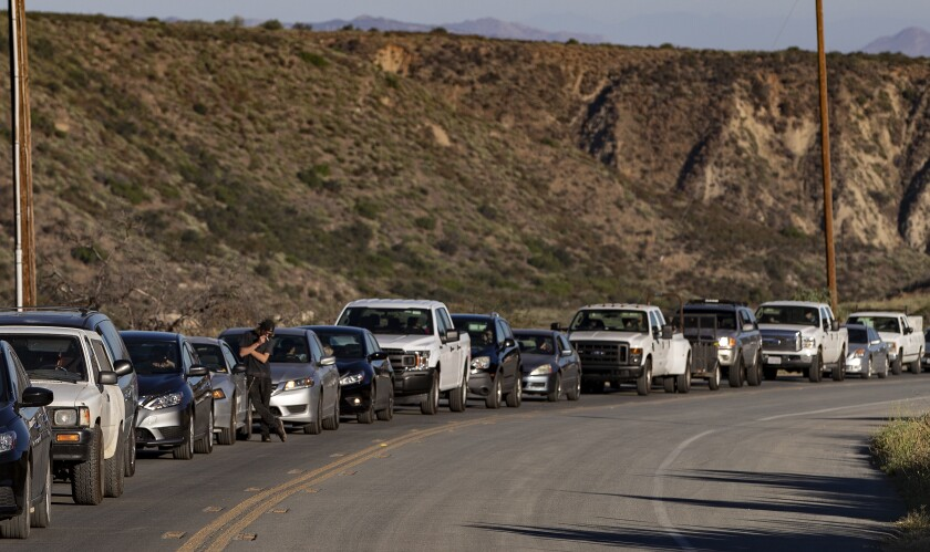 Drivers wait for a pilot vehicle to be escorted up Highway 74 in the morning to get to Idyllwild.