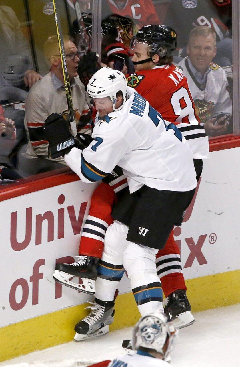 San Jose Sharks defenseman Paul Martin (7) checks Chicago Blackhawks right wing Patrick Kane into the boards during the third period of an NHL hockey game Tuesday, Feb. 9, 2016, in Chicago. The Sharks won 2-0. (AP Photo/Charles Rex Arbogast)