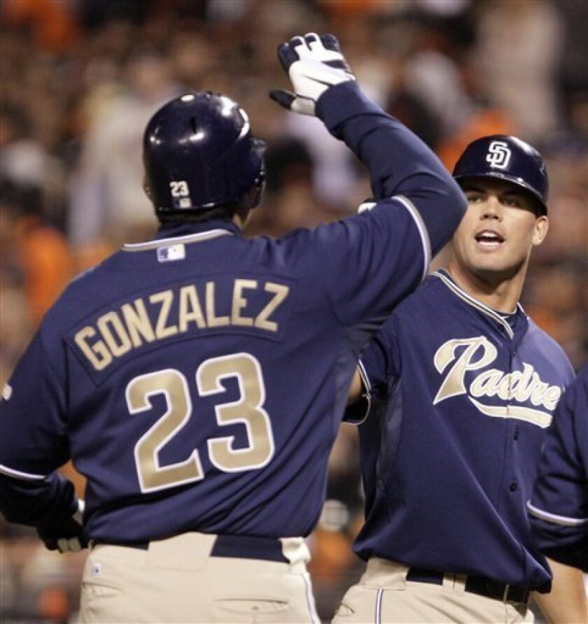 San Diego Padres' Adrian Gonzalez (23) is congratulated by pitcher Clayton Richard, center, after Gonzalez hit a three-run home run off San Francisco Giants' Matt Cain during the third inning of a baseball game Monday, Oct. 1, 2010, in San Francisco. (AP Photo/Ben Margot)