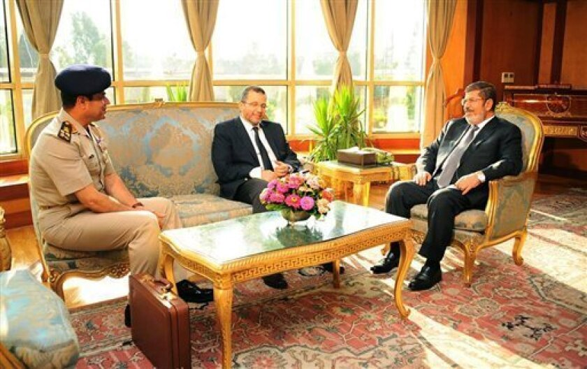 """FILE - In this file photo released by the Egyptian Presidency Monday, July 1, 2013, Egyptian President Mohammed Morsi, right, meets with Prime Minister Hesham Kandil, center, and Egyptian Minister of Defense, Lt. Gen. Abdel-Fattah el-Sissi, left in Cairo, Egypt. """"Over my dead body!"""" Mohammed Morsi told his army chief who came to him asking the Islamist president to step down on his own and not resist a military ultimatum and the demands of giant crowds out in the streets. Morsi found himself iso"""
