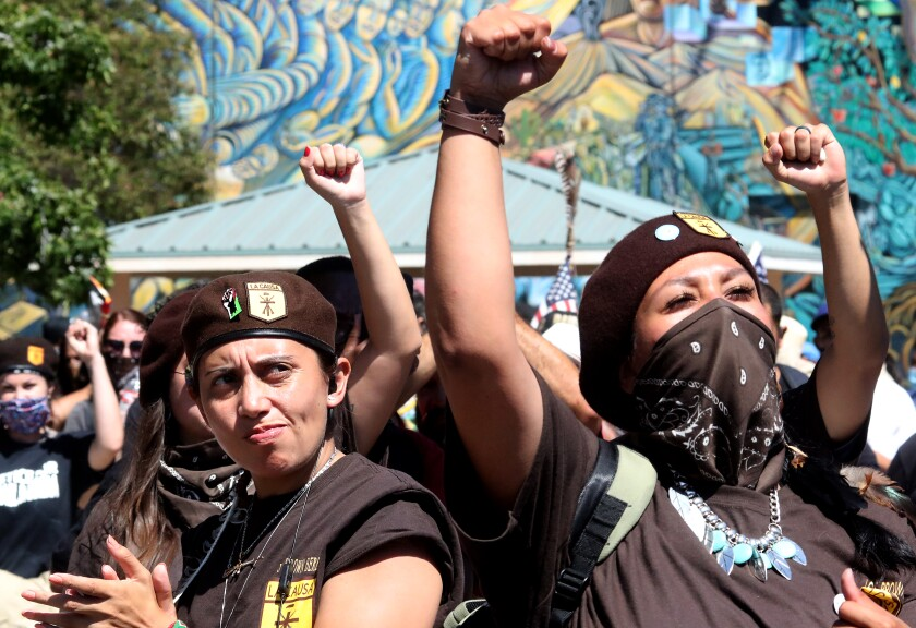 Members of the Brown Berets raise their fists in the 50th anniversary protest march of the Chicano Moratorium