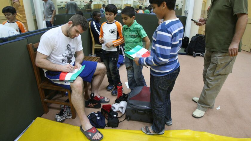 U.S. freestyle wrestler Daniel Bergman signs Iranian flags for Iranian boys during the Takhti Wrestling Cup, on the Persian Gulf island of Kish, Iran, in 2011.