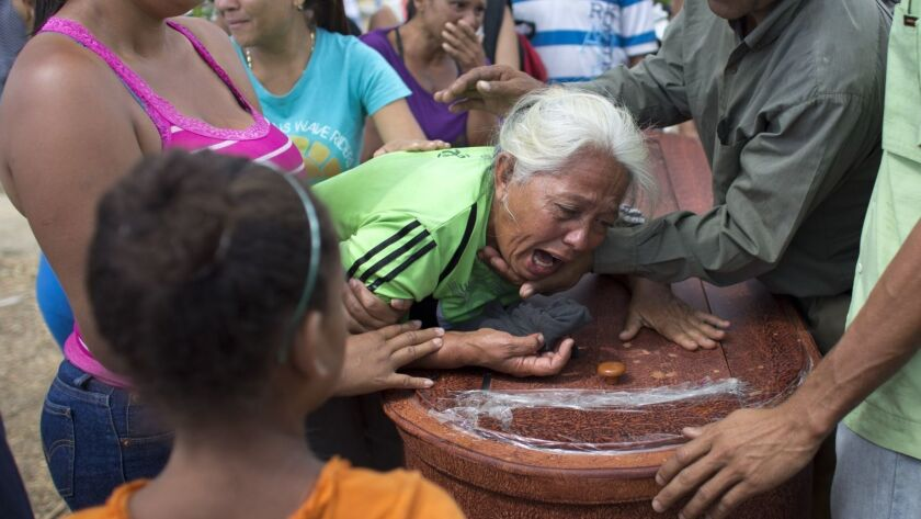 A woman grieves over the coffin containing the remains of Jose Manuel Perez, 28, at the Municipal Ce