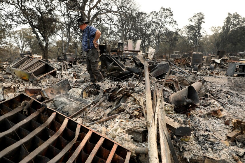 Ed Bledsoe surveys his Redding home, destroyed by the Carr fire. Bledsoe's wife, Melody, and his great-grandchildren, Emily Roberts, 5, and James Roberts, 4, were killed in the blaze.